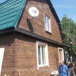 Отделка дома цокольным сайдингом под камень с деревянными наличниками